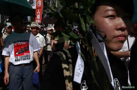 """A protester wearing a T-shirt depicting Tiananmen's """"Tankman"""" join hundreds of others in taking part in a march in Hong Kong, three days before the 25th anniversary of the military crackdown on the pro-democracy movement at Beijing's Tiananmen Square"""
