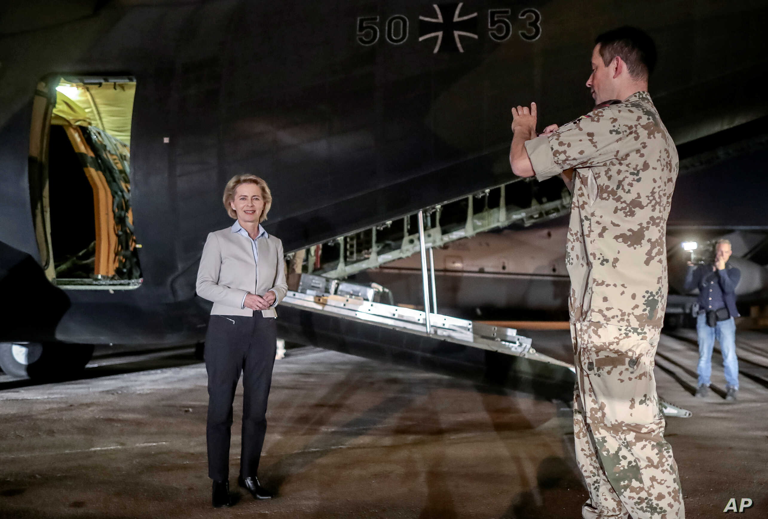 FILE - German Defense Minister Ursula von der Leyen poses in front of a German Air Force plane in Amman, Jordan, Sept. 21, 2016, on her way to Iraq.