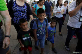 Migrant families from Mexico, fleeing from violence, walk toward the United States to meet officers of the U.S. Customs and Border Protection to apply for asylum at Paso del Norte international border crossing bridge in Ciudad Juarez June 20, 2018.