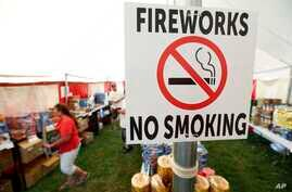 A no smoking sign is seen in an Iowa Fireworks Company tent, in Adel, Iowa. Decades after a devastating fire caused by a dropped sparkler led Iowa to ban fireworks, the explosives are now legal in the state, June 15, 2017.