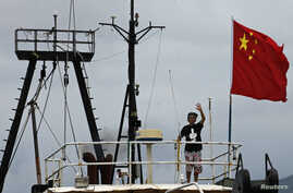 "JCaptain Why Yang of Hong Kong fishing vessel ""Kai Fung No.2"" waves next to a Chinese national flag as he reaches in Hong Kong's island of Cheung Chau, August 22, 2012."