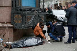 Forensic experts and police officers examine the scene following the killing of Denis Voronenkov in Kiev, Ukraine, March 23, 2017.