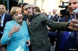 FILE - Syrian refugee Anas Modamani takes a selfie with German Chancellor Angela Merkel outside a refugee camp near the Federal Office for Migration and Refugees after registration at Berlin's Spandau district, Germany, Sept. 10, 2015.