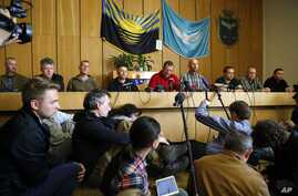 Vyacheslav Ponomaryov, the self-proclaimed mayor of Slovyansk, fourth from left, is flanked by a group of foreign military observers being held by Ponomaryov's group during a press conference in city hall, Slovyansk, eastern Ukraine, April 27, 2014.
