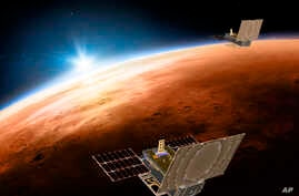 This illustration made available by NASA on March 29, 2018 shows the twin Mars Cube One (MarCO) spacecraft flying over Mars with Earth and the sun in the distance. The MarCOs will be the first CubeSats - a kind of modular, mini-satellite - flown into