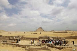 FILE - Archeologists and journalists are seen at an excavation site in Egypt.