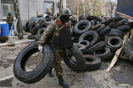 An armed man carry tires to form barricades in front of the police headquarters in Slaviansk April 12, 2014.