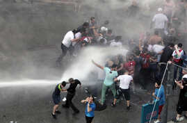 Lebanese activists are sprayed by riot police using water cannons during a protest against the ongoing trash crisis, in downtown Beirut, Lebanon, Aug. 23, 2015.