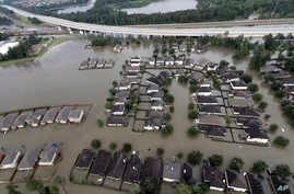 Homes are surrounded by floodwaters from Tropical Storm Harvey, Aug. 29, 2017, in Spring, Texas. Congress is considering renewing the National Flood Insurance Program.