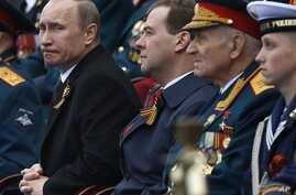 Russian President Putin and Prime Minister Medvedev, center, watch Victory Day Parade, Moscow, May 9, 2012.