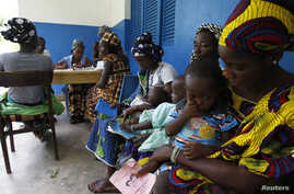 Women holding children wait for a medical examination at the health centre in Gbangbegouine village, western Ivory Coast, July 4, 2013.