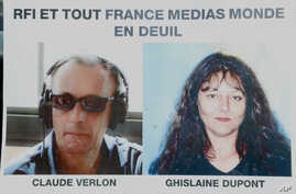 "Pictures of French RFI journalists, Ghislaine Dupont, right, and Claude Verlon on a poster headed ""RFI and all France Media World in Mourning"" displayed in a window in Paris, Nov. 3, 2013."