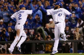 Kansas City Royals pitcher Johnny Cueto (47) celebrates with Alcides Escobar after a ground ended the seventh inning of Game 2 of the Major League Baseball World Series against the New York Mets, October 28, 2015, in Kansas City, Mo.