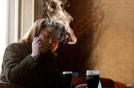 An unidentified Dubliner smokes in a pub in central Dublin, Ireland, on Jan. 30, 2003, the day Irish Health Minister Micheal Martin announced a ban on smoking in bars, restaurants and the work place.