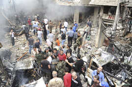 A crowd gathers in front of a building and car damaged after a bomb explosion in the Mezzeh 86 area in Damascus, in this handout photograph released by Syria's national news agency SANA, November 5, 2012.