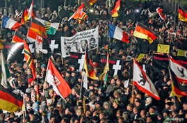 FILE - Supporters of anti-immigration movement Patriotic Europeans Against the Islamization of the West (PEGIDA) hold flags during a demonstration in Dresden, Germany, Jan. 12, 2015.