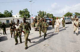 Somali soldiers patrol near the wreckage of a car bomb that was detonated at the main gate of the presidential palace in Mogadishu, July, 9, 2014.