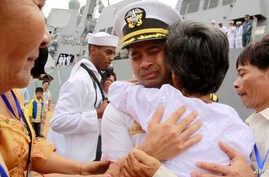 FILE - U.S. Navy Cmdr. Michael Vannak Khem Misiewicz embraces an aunt at Sihanoukville, Cambodia, upon his return to his homeland, Dec. 3, 2010. The aunt had helped arrange his adoption in the United States. Misiewicz now has been sentenced in a brib