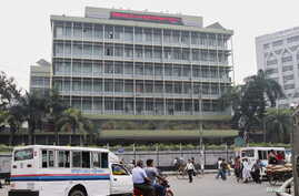 FILE - Commuters pass by the front of the Bangladesh central bank building in Dhaka.