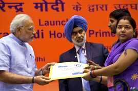 Indian Prime Minister Narendra Modi hands over a banking kit to an unidentified woman at the launch of a campaign aimed at opening millions of accounts for poor Indians in New Delhi, India, Aug. 28, 2014.