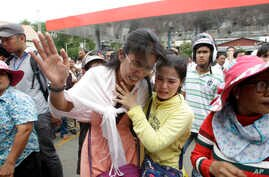 Cambodians cry outside a shopping mall where prominent political analyst Kem Ley was shot dead in Phnom Penh, Cambodia, Sunday, July 10, 2016.