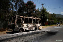 Men walk past a bus that was torched during protests in the town of Sebeta, Oromia region, Ethiopia, Oct. 8, 2016.