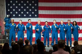 Astronauts, from left, Victor Glover, Michael Hopkins, Robert Behnken, Douglas Hurley, Nicole Mann, Christopher Ferguson, Eric Boe, Josh Cassada and Sunita Williams give a thumbs up to the crowd after NASA announced them as astronauts assigned to cre