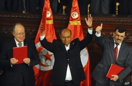 Assembly speaker Mustapha Ben Jaafar,  left, Tunisian President, Moncef Marzouki, center, and outgoing prime minister Ali Larayedh gesture after signing the new constitution into law  in Tunis, Jan.27, 2014.