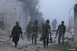 Rebel fighters from the Islamic Front walk amidst smoke during what they said was an offensive against forces loyal to Syria's President Bashar al-Assad in Maarat Al-Nouman, Idlib province, May 5, 2014.