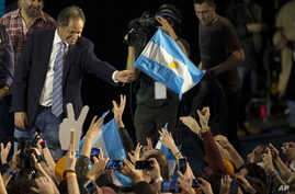 Ruling party presidential candidate Daniel Scioli holds an Argentine flag as he acknowledges supporters after primary elections in Buenos Aires, Argentina, Aug. 10, 2015.