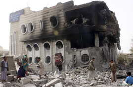 People salvage belongings from a government bank that was hit during an air strike in Yemen's northwestern city of Saada April 16, 2015. Yemeni Vice President Khaled Bahah said on Thursday he hoped a Saudi-led Arab coalition battling Iranian-allied H