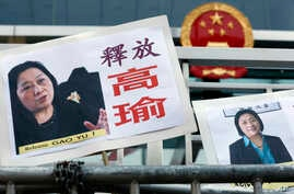 Pictures of jailed veteran Chinese journalist Gao Yu are displayed by protesters outside Chinese central government's liaison office in Hong Kong Friday, April 17, 2015.