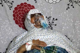 A woman breathes through an oxygen mask at al-Quds hospital, after a hospital and a civil defence group said a gas, what they believed to be chlorine, was dropped alongside barrel bombs on a neighbourhood of the Syrian city of Aleppo, Syria, August 1
