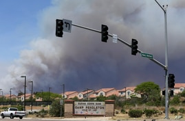 Smoke plumes rise behind the Marine Corps Camp Pendleton entrance Friday, May 16, 2014, in Oceanside, Calif.