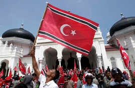 An Acehnese man waves a Crescent-Star flag during a rally outside Baiturrahman Grand Mosque in Banda Aceh, Aceh province, Indonesia, April 1, 2013.