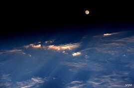 """Expedition 48 Commander Jeff Williams of NASA took this photograph on June 21, 2016, from the International Space Station, writing, """"A spectacular rise of the full moon just before sunset while flying over western China."""""""