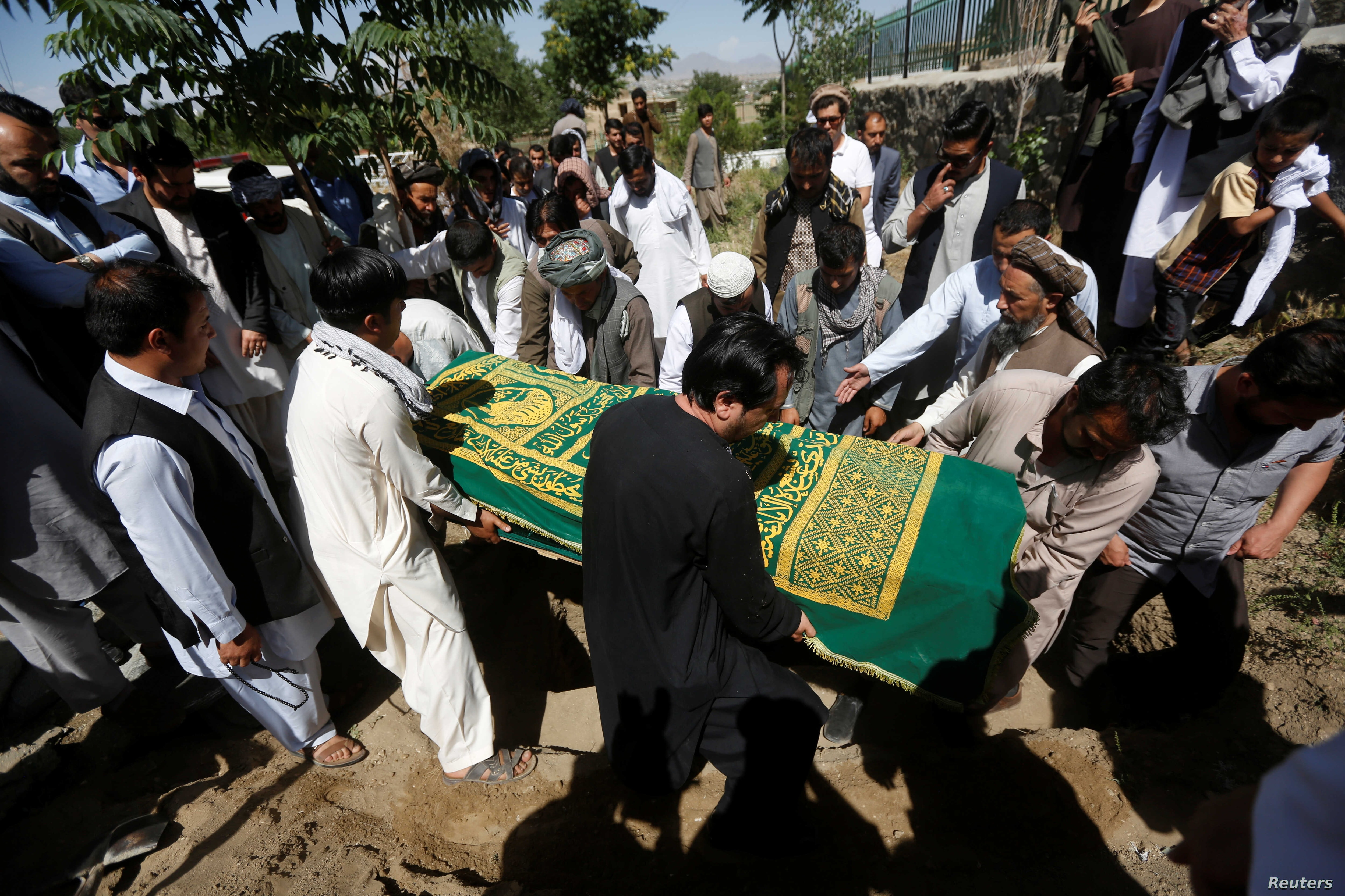 FILE - Afghans take part in the burial of an Afghan journalist in Kabul, Afghanistan June 7, 2016. A roadside bomb killed one journalist and wounded another Friday. 2016 is the deadliest year yet for journalists in Afghanistan.