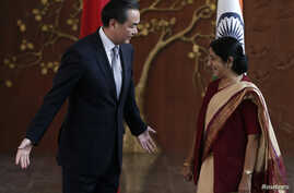 Chinese Foreign Minister Wang Yi (L) gestures to his Indian counterpart Sushma Swaraj before their meeting in New Delhi, June 8, 2014.