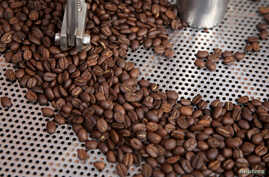 FILE - Coffee beans are seen in a roaster at a stand at the Coffee Fair in Lima, Peru.