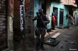 A military police officer patrols the Kelson's slum during an operation against crime in Rio de Janeiro, Brazil, Feb. 20, 2018.