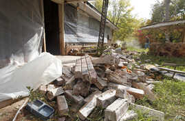 FILE - Chad Devereaux works to clear up bricks that fell from three sides of his in-laws' home in Sparks, Okla., after two earthquakes hit the area in less than 24 hours, April 6, 2011.
