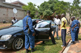 Burundi police officers inspect the vehicle of minister Hafsa Mossi, a close ally of President Pierre Nkurunziza, after she was killed on July 13, 2016 in Burundian capital, Bujumbura, according to the police spokesman, Pierre Nkurikiye.  Mossi, a cu