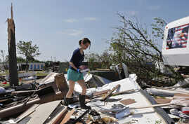 Dillan Taylor salvages items from her storm-ravaged recreational vehicle in Oklahoma City, May 7, 2015.
