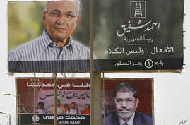 Giant billboards showing Egyptian presidential candidates Ahmed Shafiq, top, and Mohamed Morsi, bottom, are seen along a highway in Cairo, June 11, 2012.