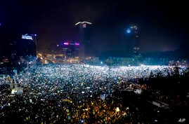 Tens of thousands of people shine lights from mobile phones and torches during a protest in front of the government building in Bucharest, Romania, Sunday, Feb. 5, 2017.