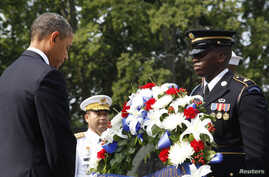 U.S. President Barack Obama (L) bows his head after laying a wreath on the 60th anniversary of the end of the Korean War, at the Korean War Veterans Memorial in Washington, July 27, 2013.