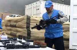 FILE - In this photo released by the United Nations mission based in Colombia, a member of U.N. monitoring mission for the Colombian peace process holds a weapon handed over by rebels of the Revolutionary Armed Forces of Colombia, FARC, as part of la