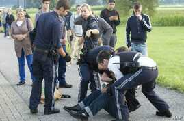 Austrian policemen arrest a suspect on August 16, 2016 at the train station Sulz-Röthis in Vorarlberg, Austria, after he had attacked two train passengers with a knife.
