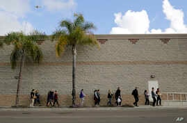 Volunteers carry donated items towards a group of undocumented migrants looking for work as day laborers alongside a hardware store in San Diego, California, Feb. 4, 2017.