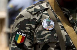 A soldier wears a button bearing the image of coup leader Capt. Amadou Haya Sanogo with the words 'President, CNRDRE,' the French acronym of the ruling junta, outside Bamako, Mali, April 1, 2012.